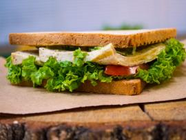 Plant-based tempeh lettuce and tomato sandwich on a rustic setting.
