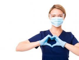 health care worker in PPE making heart symbol with two hands in gratitude