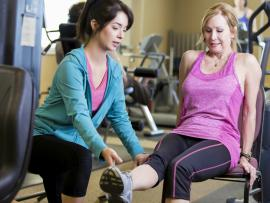 trainer helping woman exercise at the gym
