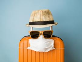 suitcase, mask, sunglasses and straw hat arranged to look like a vacationing person