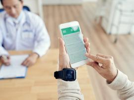 senior patient using wearable fitness device at doctor's office