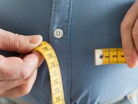 overweight man measuring his stomach with a measuring tape
