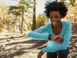 african american woman in workout clothes looking at watch