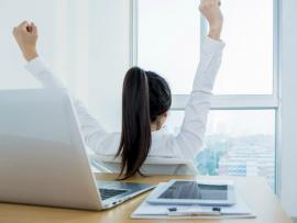 woman sitting at desk at work and stretching her arms out