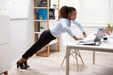 Young businesswoman does a pushup on her desk in her office.