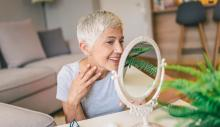 Woman smiles as she examines her skin in a mirror.