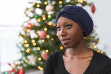 African-American woman with cancer wearing turban sitting in front of Christmas tree