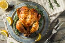 A whole rotisserie chicken on a plate, surrounded by lemon wedges and fresh rosemary.
