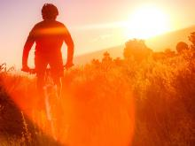 Man riding bike in sunset_4 ways to improve your health in the new year