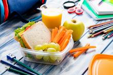 Healthy lunch of a sandwich, apple, carrots and orange juice arranged in a plastic container, on a table surrounded by colored pencils and other school supplies, with an insulated lunch bag in the background.