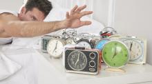 man in bed reaching to turn off multiple alarm clocks