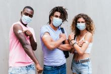 three millennials with masks showing their arms with vaccine bandaids