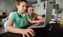 boy sitting at laptop with father