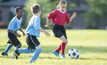 girl and two boys playing soccer