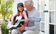 grandfather teaching his granddaughter how to play guitar