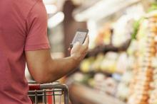 closeup of man's arm holding phone displaying shopping list in grocery store