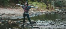 happy woman with outstretched arms crossing a stream