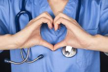 chest view of medical person making heart shape with hands over scrubs and stethoscope
