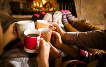 group of friends drinking hot drinks in front of a fire and living the hygge life.