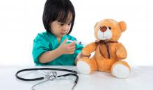 little girl dressed as a doctor giving a shot to her teddy bear