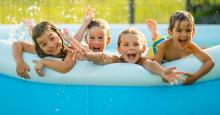 young kids playing in backyard inflatable pool
