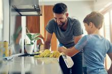 A young boy helps his father clean a kitchen countertop with a spray bottle.