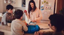mom packing snacks for school while kids sit around kitchen table