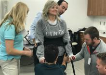 Pam Cobler with Carilion Clinic's Physical Therapy team helping her learn how to use ReWalk.