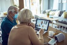 senior couple researching hospice on laptop with masks on