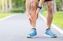 view of male legs on running path with hands gripping right shin indicating pain
