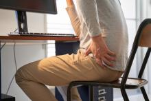 view from side of man with sore back sitting on folding chair in makeshift home office