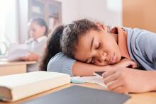 adolescent girl asleep at her desk at school