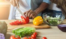 View of man's hands holding a knife slicing peppers for a bowl of salad. A woman stands beside him.