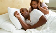 man snoring in bed and keeping wife awake.
