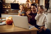 young family blowing kisses to distant relatives via computer