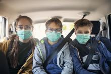 3 kids in back seat of vehicle wearing surgical face masks