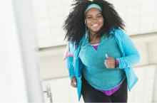 young african american woman smiling and running as she works out