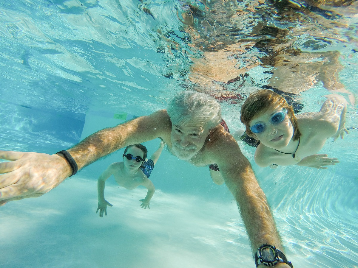 underwater image of two children with goggles and a senior man in a swimming pool