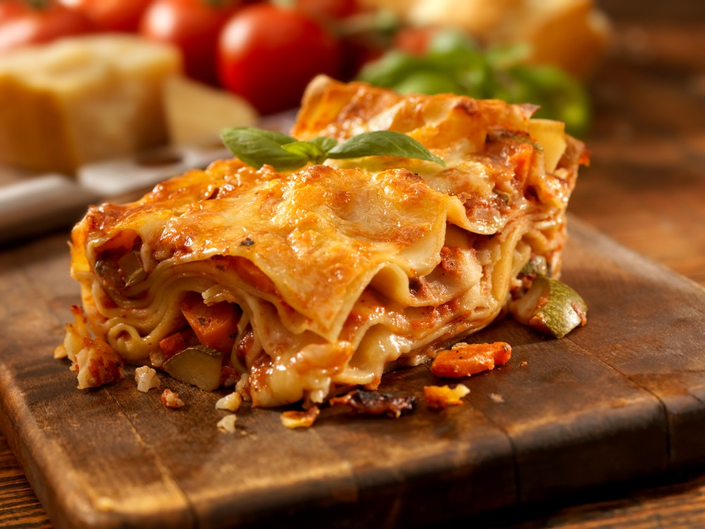 A slice of homemade vegetarian lasagna sits on a wooden cutting board.