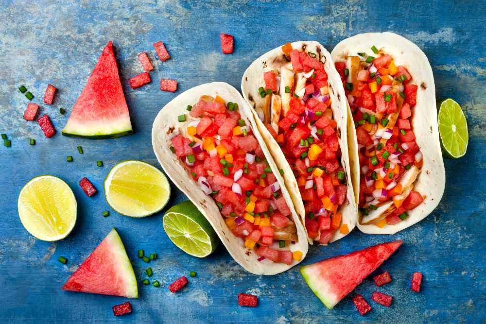 Tortillas filled with watermelon salsa, beside watermelon and citrus slices, on a bright blue background.